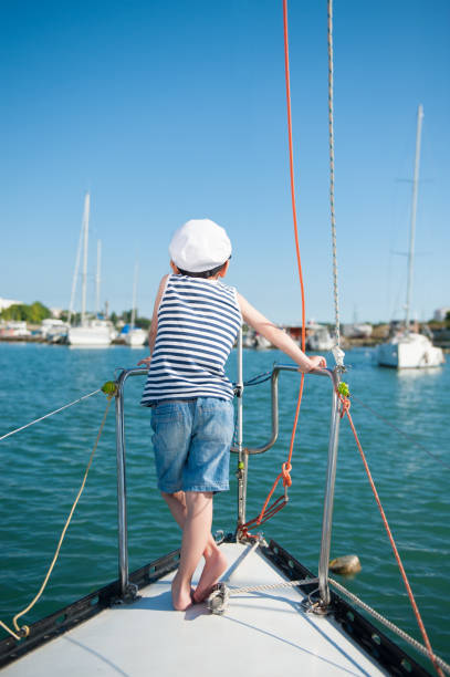 dreaming kid captain aboard luxury yacht dreaming kid captain aboard luxury yacht looking forward sailor hat stock pictures, royalty-free photos & images