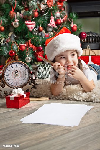 1062609644istockphoto Dreaming little girl dreams about the gift and writes letter 495902760