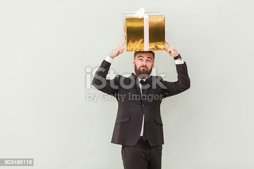 istock Dreaming or idea concept. Thoughtful businessman dreams and holding box 903486116