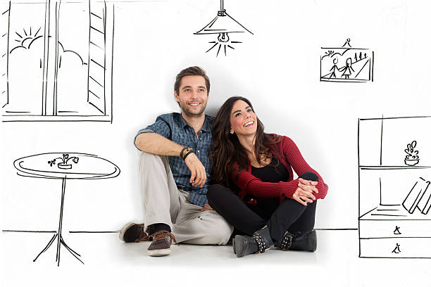 Dreaming Young couple sitting on floor looking up while dreaming their new home and furnishing. model home stock pictures, royalty-free photos & images