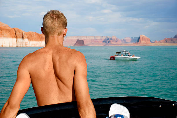 Dreaming Wakeboarder Young man holding a wakeboard looking across the lake lake powell stock pictures, royalty-free photos & images