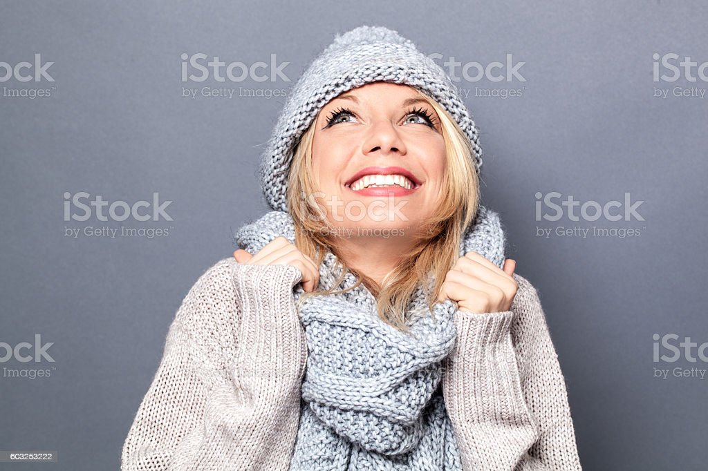 dreaming young blond woman with winter hat and imagination stock photo