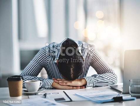 Shot of a young businesswoman lying with her head down on a desk in an office