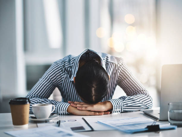 Dreamland is better than all these deadlines Shot of a young businesswoman lying with her head down on a desk in an office mental burnout stock pictures, royalty-free photos & images
