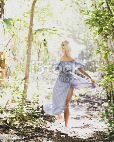A young woman in a beautiful blue dress spins and dances on a wilderness trail soaked in sunlight. Very soft focus to convey dreamlike quality