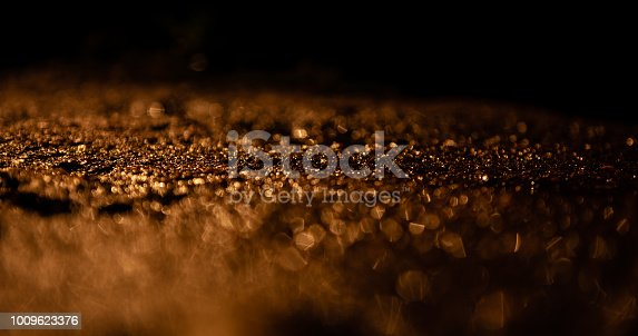 Extreme close-up shot of wet asphalt/concrete, creating a glittering effect.  Useful for background(s).