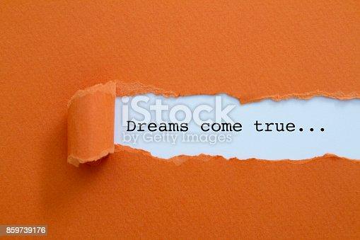 Dreams come true written under torn paper.