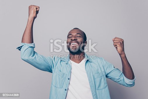 istock Dreams come true! Portrait of excited cheerful handsome delightful joyous wearing casual denim shirt guy raising his hands up, isolated on grey background 925444368