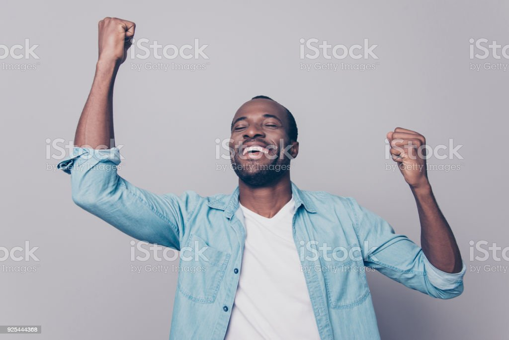 Dreams come true! Portrait of excited cheerful handsome delightful joyous wearing casual denim shirt guy raising his hands up, isolated on grey background stock photo