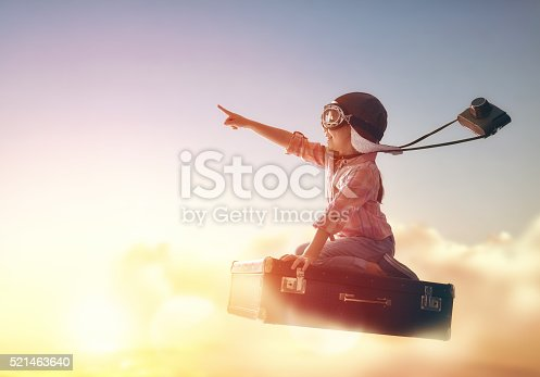 Dreams of travel! Child flying on a suitcase against the backdrop of a sunset.