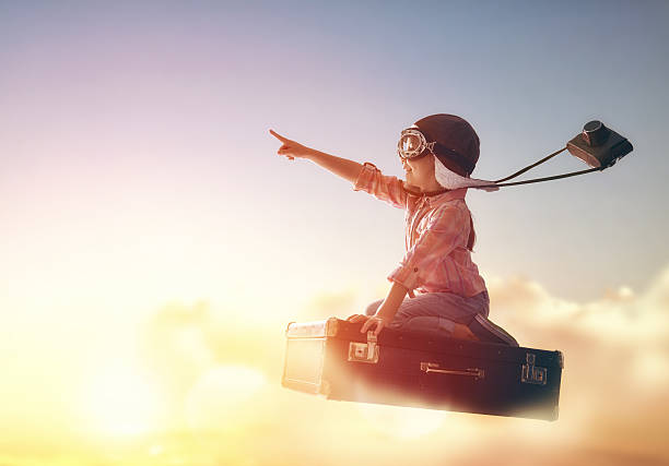 Dreams of travel Dreams of travel! Child flying on a suitcase against the backdrop of a sunset. dreamlike stock pictures, royalty-free photos & images