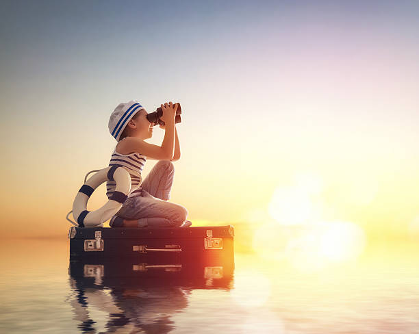 Dreams of travel Dreams of travel! Child floats on a suitcase against the backdrop of a sunset. sailor stock pictures, royalty-free photos & images