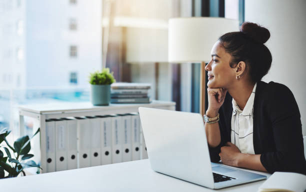 Dreams will get you far Shot of a young businesswoman using a laptop at her desk in a modern office and looking thoughtful looking at view stock pictures, royalty-free photos & images