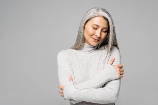 dreamy asian woman in turtleneck with grey hair and closed eyes isolated on grey stock photo