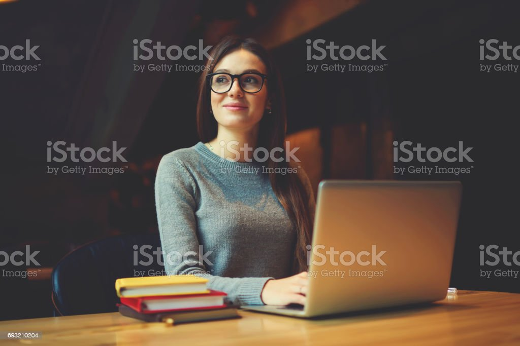 Dreamy attractive female student thinking about coursework strategy stock photo
