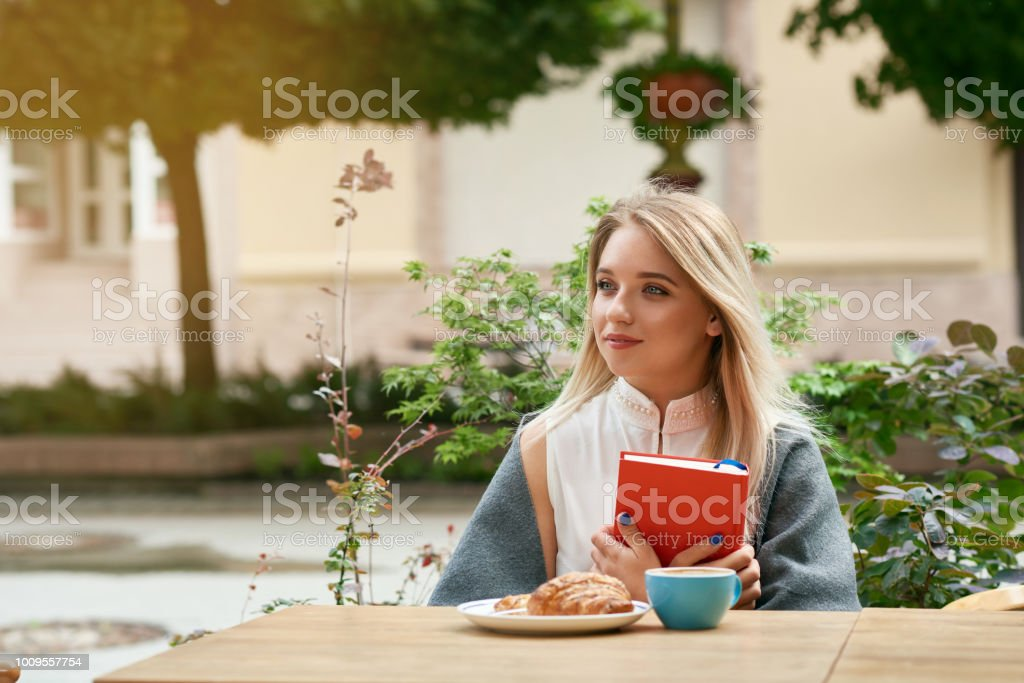 Dreamy blonde girl keeping red book sitting outdoors. stock photo