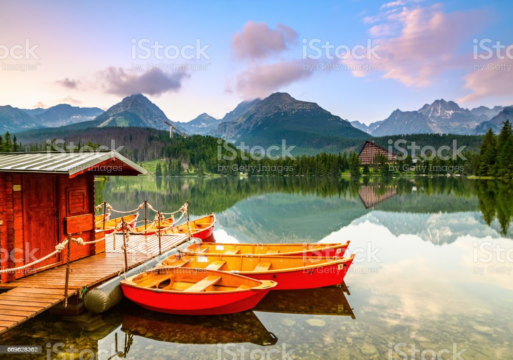 Dreamy boats stand near wooden bridge and a hut on a mountain lake on a spring day.Strbske Pleso lake, Slovakia, Tatra mountains. stock photo