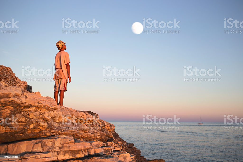 dreamy boy admires enchanted moon in the sky Lizenzfreies stock-foto