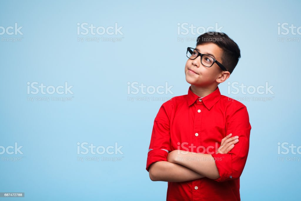 Dreamy boy with arms crossed stock photo