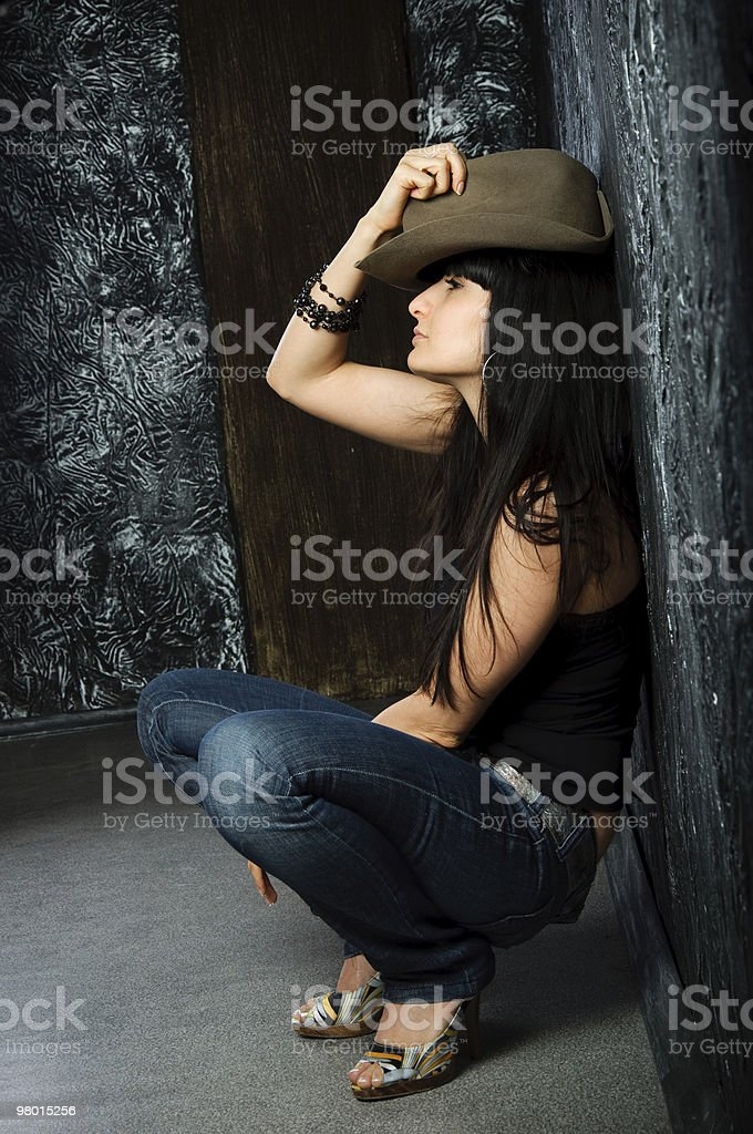dreamy brunette woman squats and a hat holding royalty-free stock photo