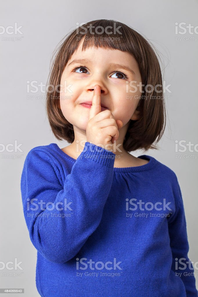 dreamy cute young girl playing with her finger on lips stock photo