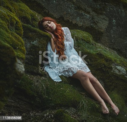 Dreamy girl sleeping in the forest