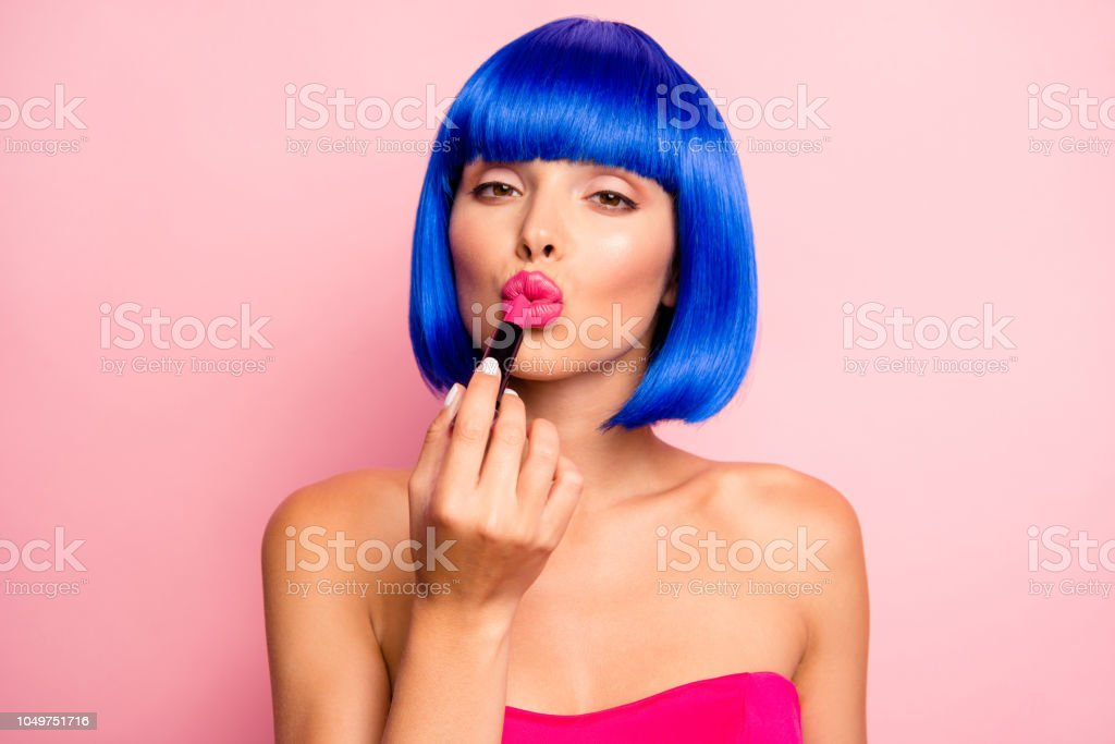 Dreamy girl with modern hairdro, ideal face prepare for date and painting her augmentation lips isolated on pastel background stock photo
