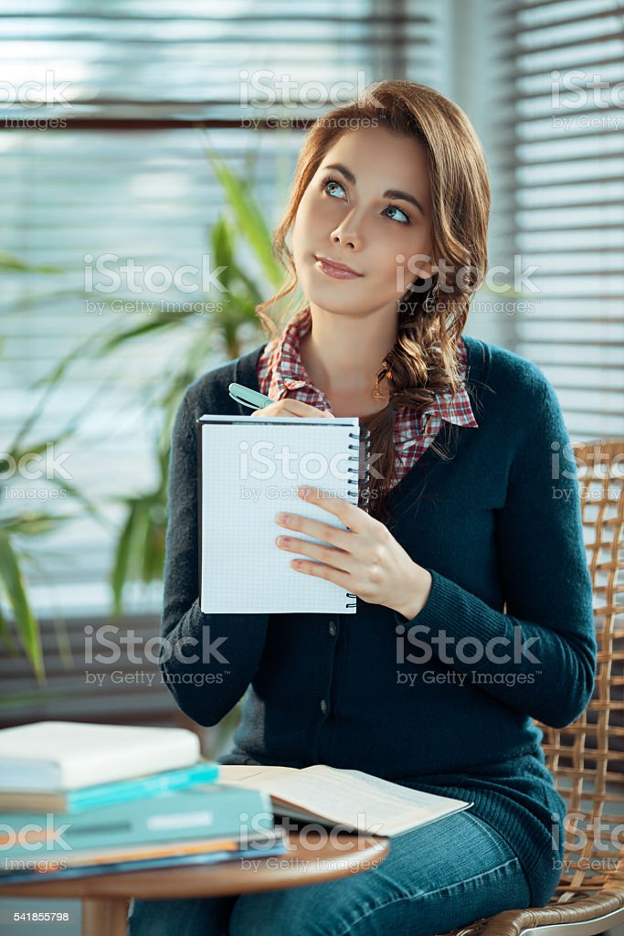 Dreamy girl writing stock photo
