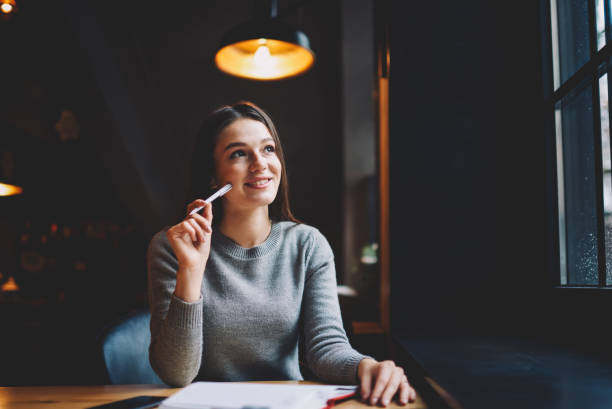 Dreamy hipster girl with pen in hand thinking on creative ideas for writing interesting article sitting at table with notepad in coworking.Thoughtful smiling student pondering on plans on future stock photo