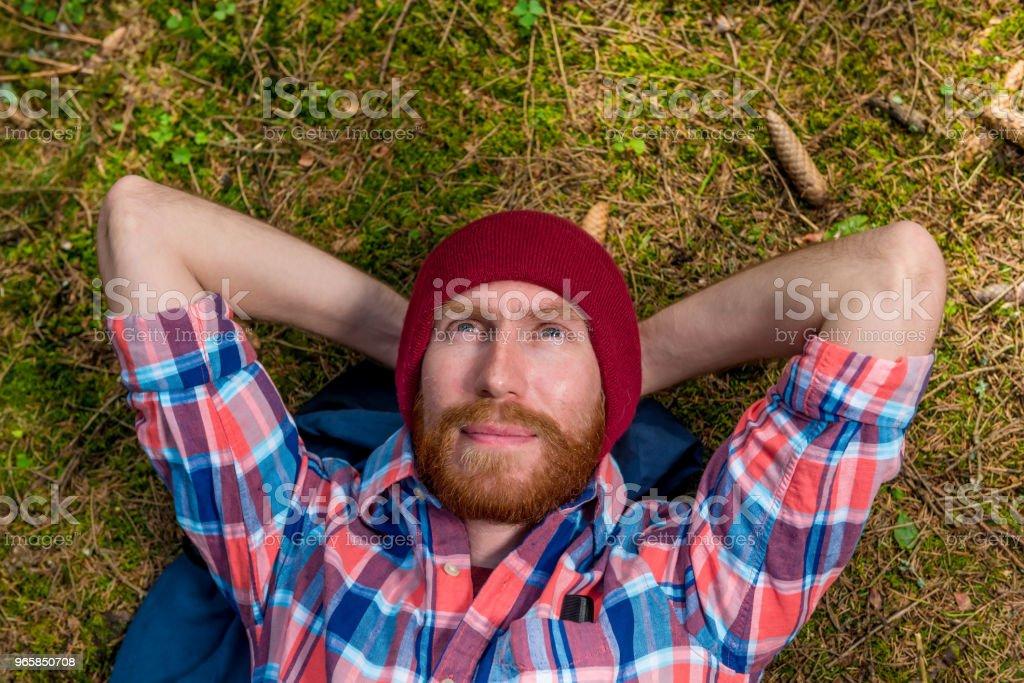 dromerige hipster op de grond in het bos, rust en kijken naar de hemel - Royalty-free Alleen mannen Stockfoto