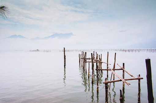 Old bamboo pier leading out in the mystic sea