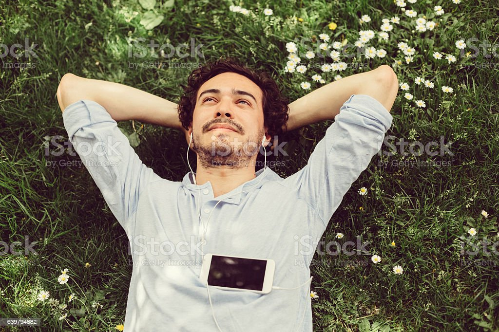 Dreamy man in the grass Young man relaxing in the grass and enjoying the music Adult Stock Photo