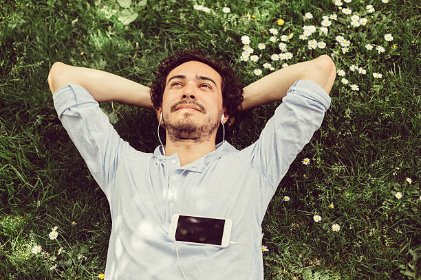dreamy man in the grass - casque audio photos et images de collection