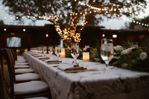 A Dreamy Outdoor Dinner Setting A Dreamy Outdoor Dinner Setting at dusk with bistro lights courtyard stock pictures, royalty-free photos & images
