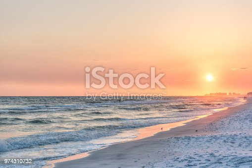 Dreamy pink peach orange sunset in Santa Rosa Beach, Florida with Pensacola coastline coast cityscape skyline in panhandle with ocean gulf mexico waves, birds