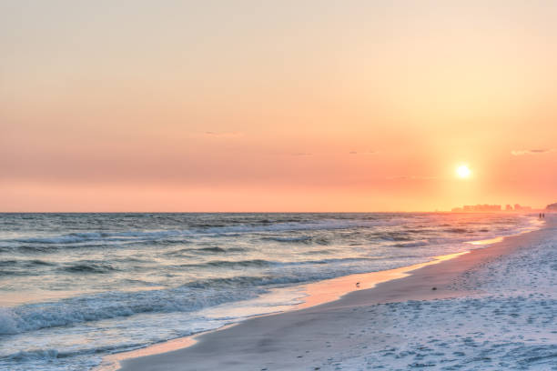 Dreamy pink peach orange sunset in Santa Rosa Beach, Florida with Pensacola coastline coast cityscape skyline in panhandle with ocean gulf mexico waves, birds stock photo