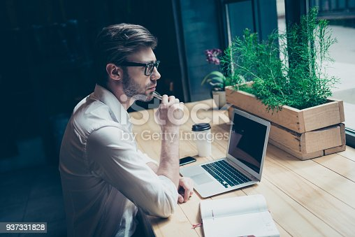 937328186 istock photo Dreamy ponder young man in formal wear is sitting at his work place in a loft styled modern coworking and looks at the window, thinking 937331828