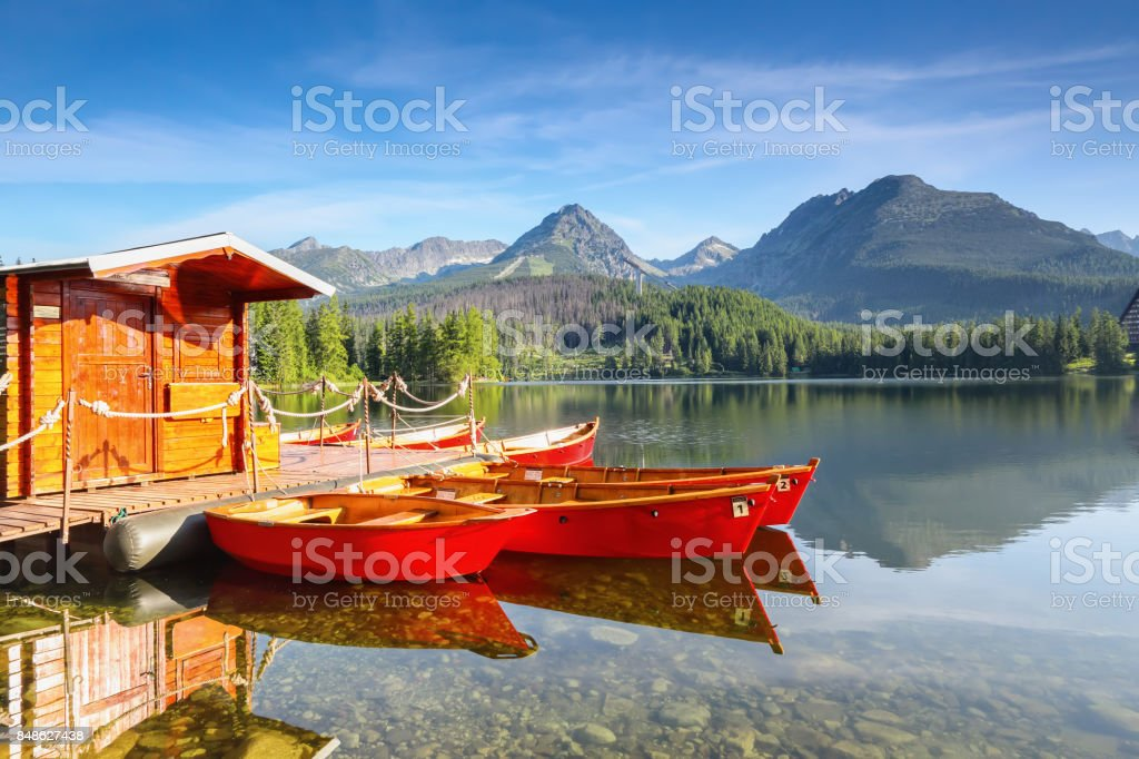 Dreamy red boats stand at the pier on a quiet lake with a beautiful view of the mountains.Strbske Pleso lake, Slovakia, Tatra mountains. stock photo