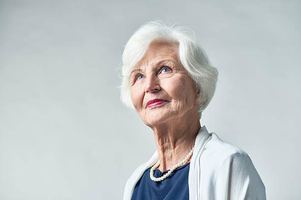 dreamy senior woman in elegant garment - mujeres mayores fotografías e imágenes de stock