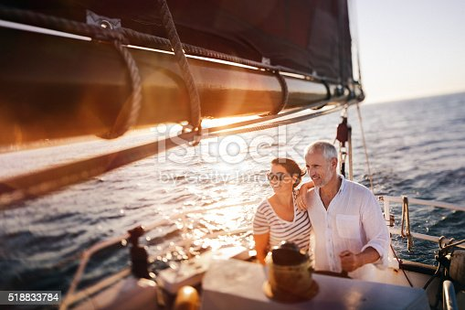 Dreamy vignate shot of senior active couple enjoying the fresh ocean breeze on their leasure cruise on their yacht