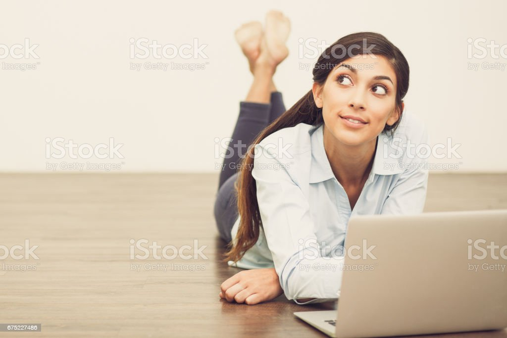 Dreamy Woman Lying on Floor and Working on Laptop royalty-free stock photo