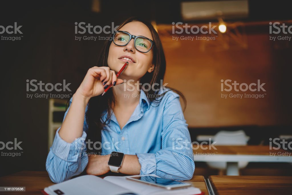 Dreamy woman podring while working on journalistic publication sitting with notebook in cafe,thoughtful female student in eyewear doing homework task solving problems and analyzing information Dreamy woman podring while working on journalistic publication sitting with notebook in cafe,thoughtful female student in eyewear doing homework task solving problems and analyzing information Contemplation Stock Photo