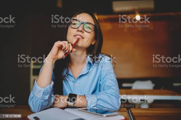 Photo of Dreamy woman podring while working on journalistic publication sitting with notebook in cafe,thoughtful female student in eyewear doing homework task solving problems and analyzing information