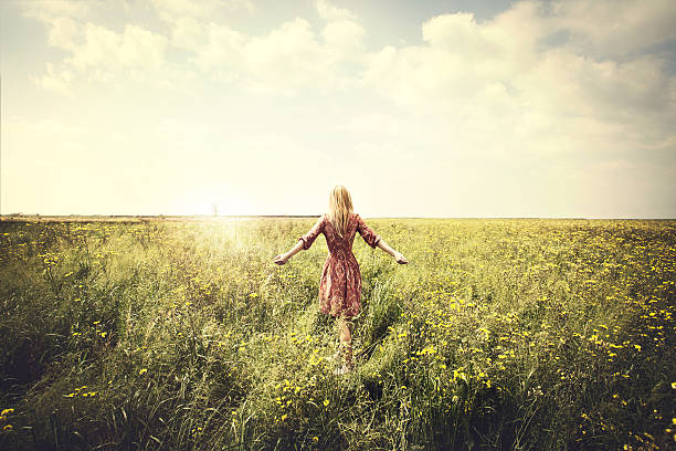 dreamy woman walking in nature towards the sun stock photo