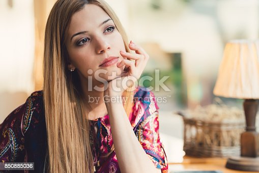 istock Dreamy woman with hand on chin looking through the window 850885036