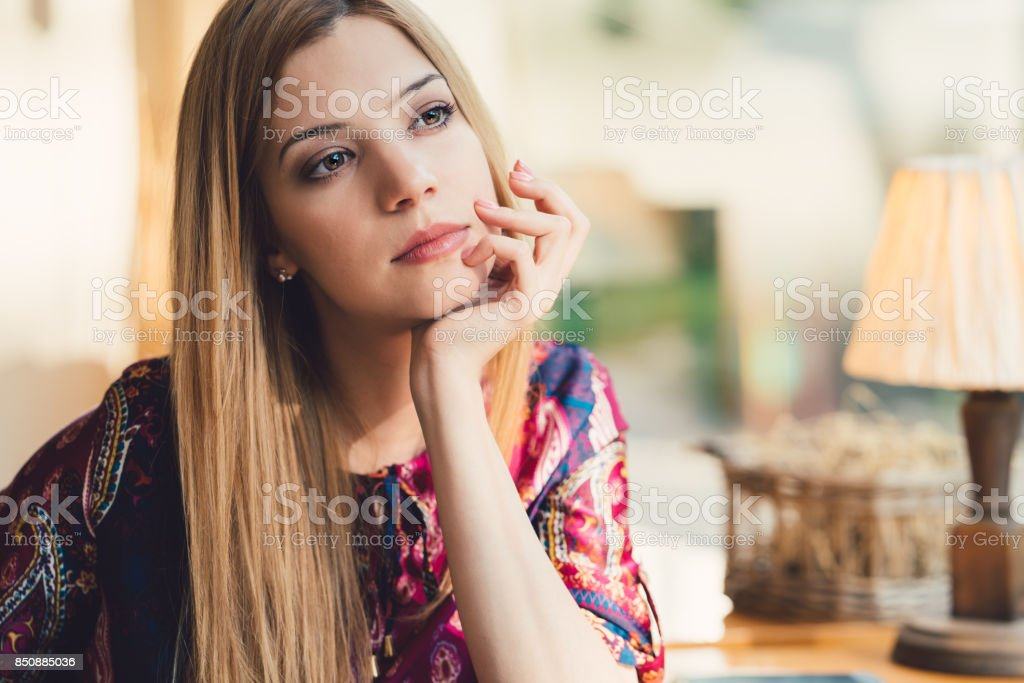 Dreamy woman with hand on chin looking through the window stock photo