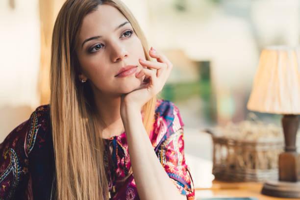 dreamy woman with hand on chin looking through the window - mano sul mento foto e immagini stock