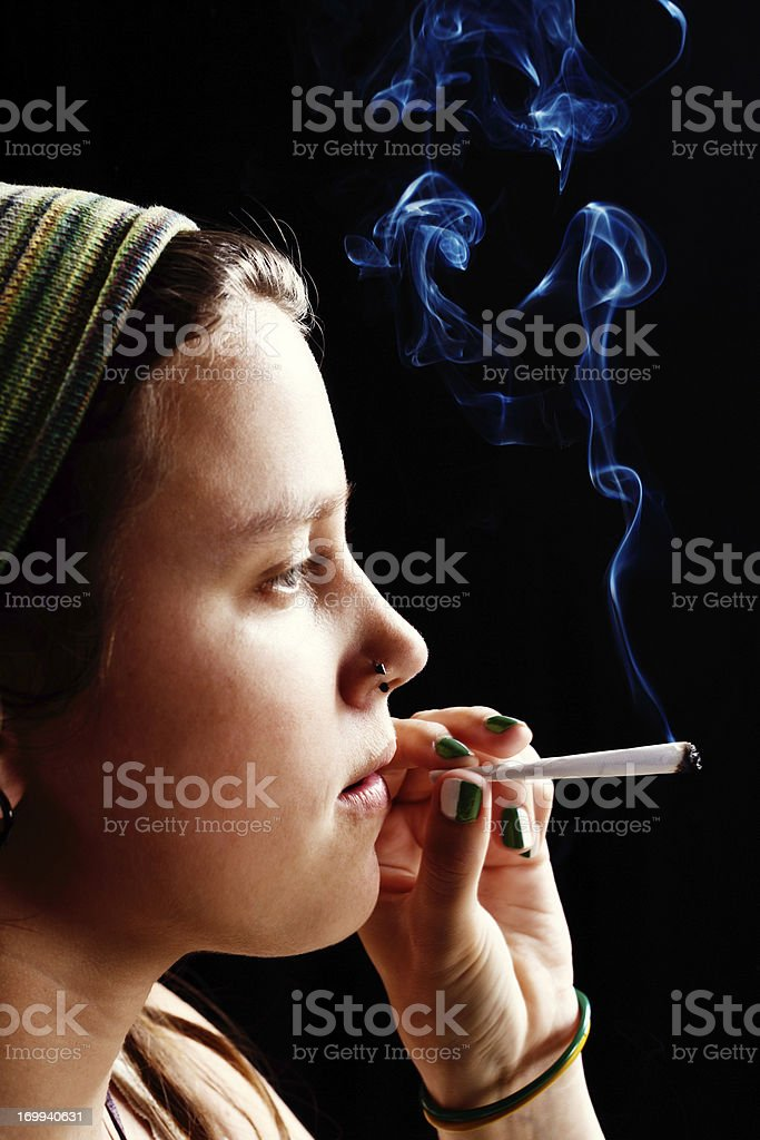 Dreamy young woman about to puff on marijuana cigarette stock photo