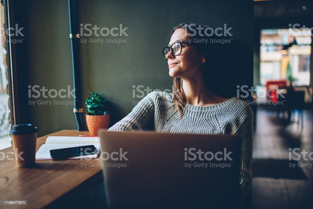 Dreamy young woman freelancer looking out of window and thinking on...