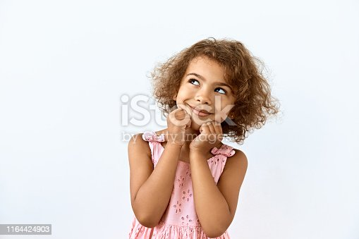 istock Dreamy,pleased, thinking emotion . Wish concept. Little African American girl face portrait on white backgound. 1164424903